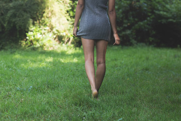 Rear view of lower body of model walking on grass holding dress