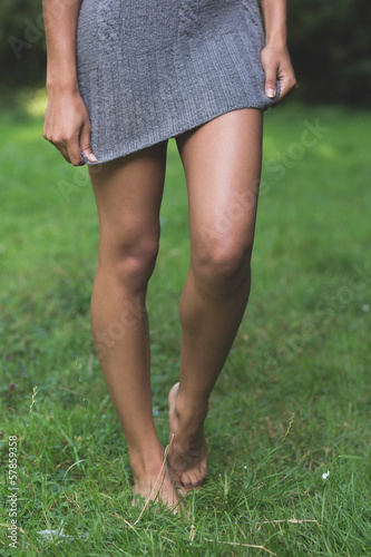 Lower body of attractive model walking on grass pulling down dress