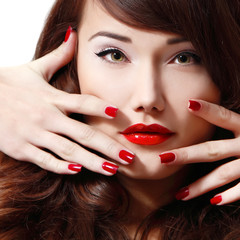 young woman portrait with long hair, red lipstick and manicure