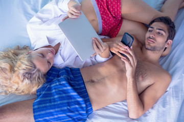Young couple lying on their bed playing with electrical devices