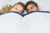 Beautiful woman hiding under a blanket with her boyfriend
