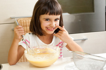 Cute and happy little girl cooking a cake