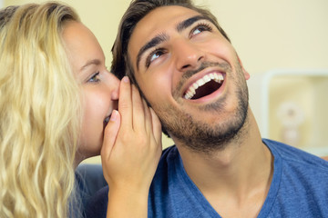 Blonde cute woman whispering something to her boyfriend