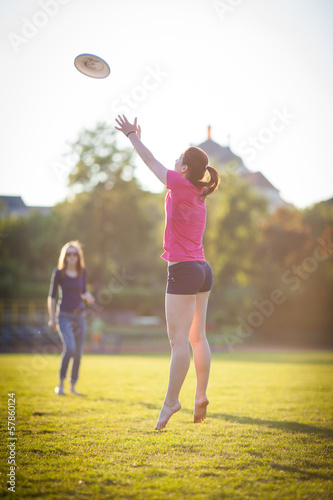 Young girl is catching a frisbee at summertime