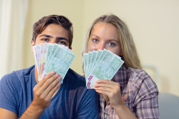 Beautiful young couple hiding their faces behind cash