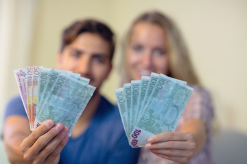 Cheerful couple showing money