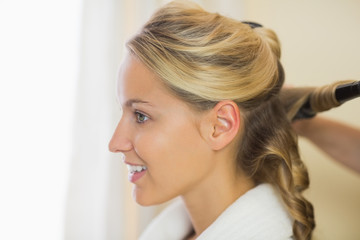 Blonde cute woman having her hair done