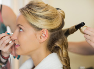 Young woman having her hair done and makeup done