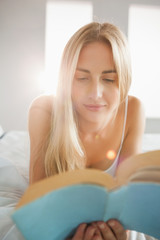 Smiling blonde reading a book on her bed