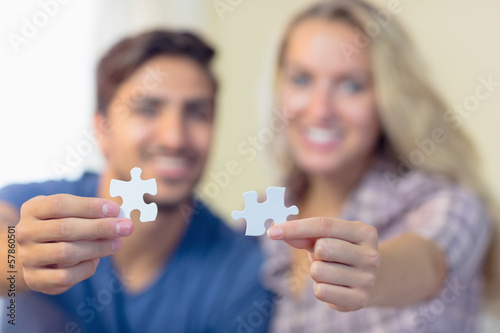 Cheerful young couple showing jigsaw pieces