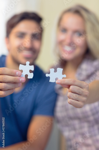 Attractive smiling couple showing jigsaw pieces