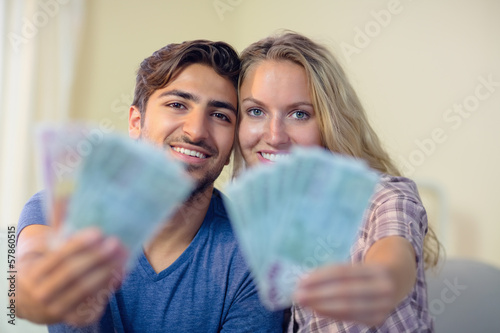 Happy couple showing some money