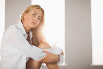 Pretty blonde wearing mens shirt sitting on bed pouting at camera