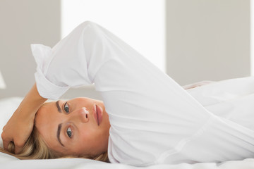 Peaceful blonde wearing white shirt lying on bed