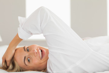 Laughing blonde wearing white shirt lying on bed