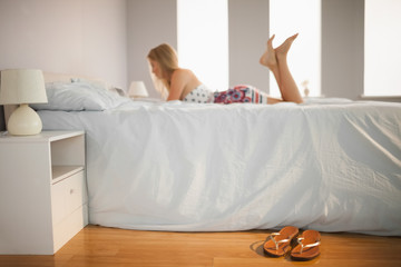 Woman lying on bed with flip flops on the floor beside