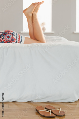 Woman lying on bed with flip flops on the floor