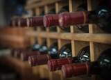 Red wine bottles stacked on wooden racks