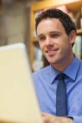 Smiling librarian working at laptop