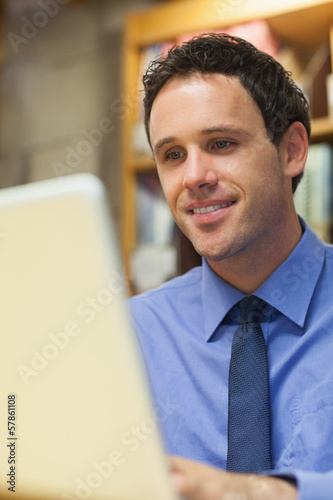 Smiling librarian working at laptop