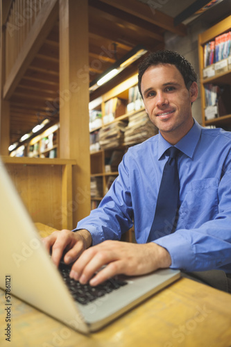 Cheerful librarian working at laptop