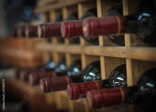 Red wine bottles stacked on wooden racks - 57861179