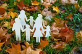 paper family in autumn grass