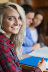 Blonde cheerful student studying with other students
