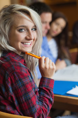 Blonde happy student studying with other students