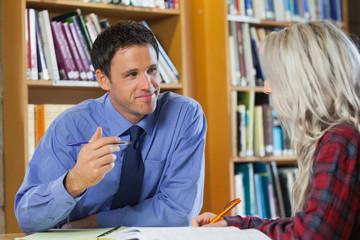 Smiling lecturer explaining something to blonde student