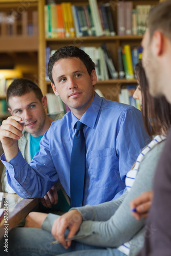 Attractive lecturer explaining something to group of students