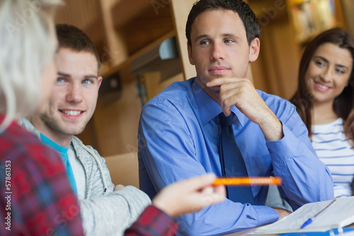 Focused lecturer explaining something to group of students