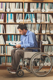 Focused man sitting in wheelchair reading a book