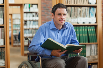 Content man in wheelchair holding a book