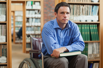 Serious man in wheelchair holding a book