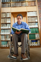 Calm man in wheelchair holding a book