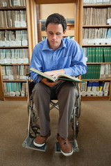 Calm man in wheelchair looking at a book