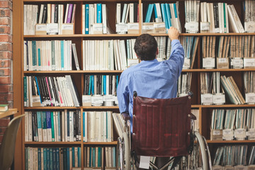 Man in wheelchair taking a book out of bookshelf