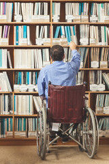 Man in wheelchair putting back a book in bookshelf