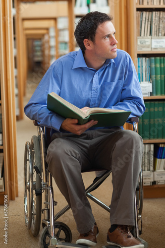 Thoughtful man in wheelchair holding a book