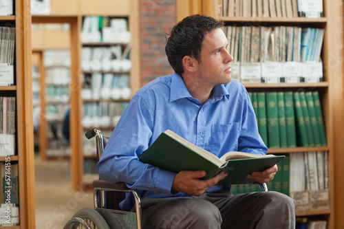 Pensive man in wheelchair holding a book