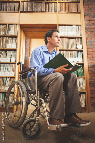 Day dreaming man in wheelchair holding a book