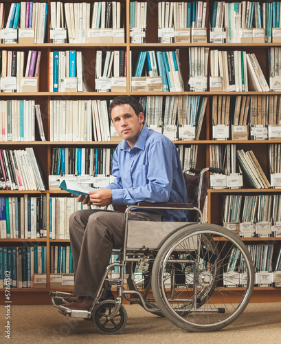 Calm man sitting in wheelchair holding a book