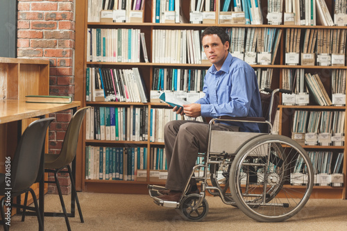 Serious man sitting in wheelchair holding a book
