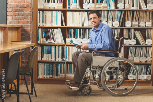 Happy man sitting in wheelchair holding a book