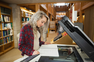 Focused blonde student standing next to photocopier
