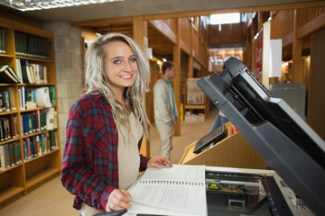 Cheerful blonde student standing next to photocopier
