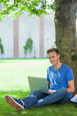 Cheerful handsome student sitting under tree using laptop
