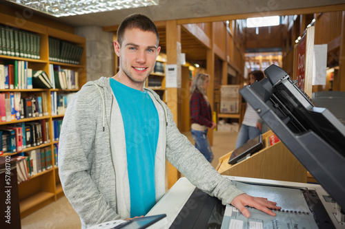 Happy good looking student using photocopier