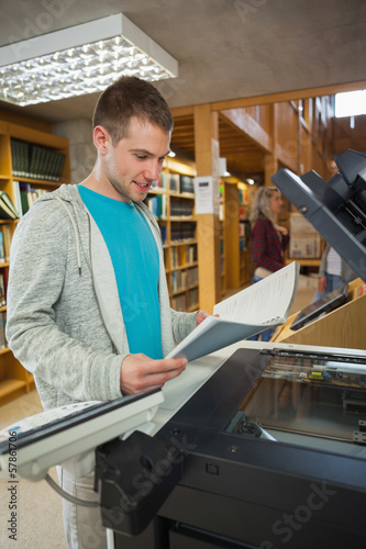 Happy good looking student standing next to photocopier